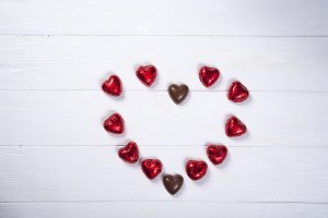 heart made of chocolates on white wooden background