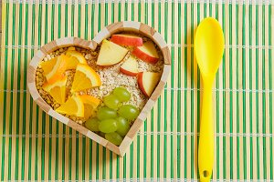 mixed fruits in heart shaped bowl. Healthy food concept