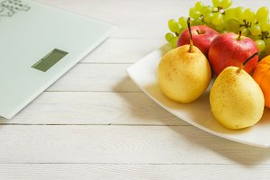 floor scale and fruits on wooden background