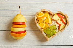 Fruits heart on the wooden background. Healthy food concept.
