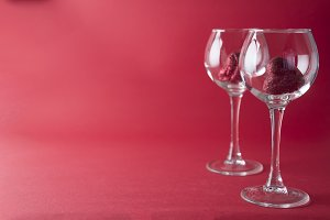 Red hearts in a glasses isolated on red background