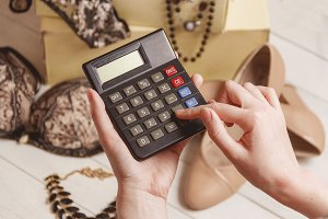 consumerism and sale concept - calculator, women clothing, accessories.