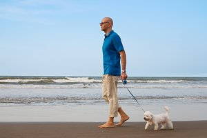 Man walking with maltese dog
