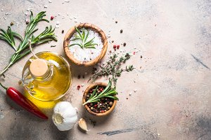 Spices and herbs background - olive oil rosemary on stone table.