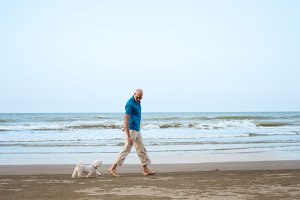 Man walking with dog on the beach