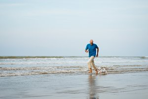 Man and dog running in the water
