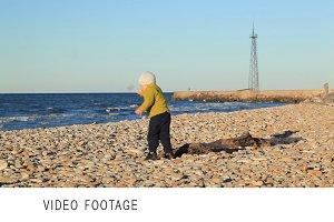 Little boy on pebble beach.