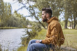 Man sitting by the river in fall.
