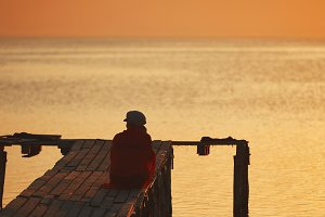silhouette of a aged womanl against the sea and sunset