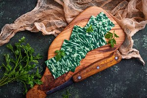 Green sliced cheese with herbs.