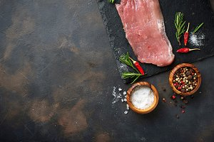 Raw meat steak with spices on rusty background