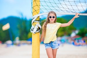 Little adorable girl playing beach volleyball with ball. Sporty family enjoy beach game outdoors