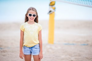 Little adorable girl playing beach volleyball. Sporty family enjoy beach game outdoors