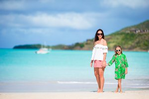 Beautiful mother and daughter at Caribbean beach enjoying summer vacation