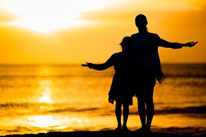 Little girl and happy mother silhouette in the sunset at the beach