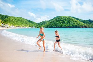 Kids having fun at tropical beach during summer vacation playing together