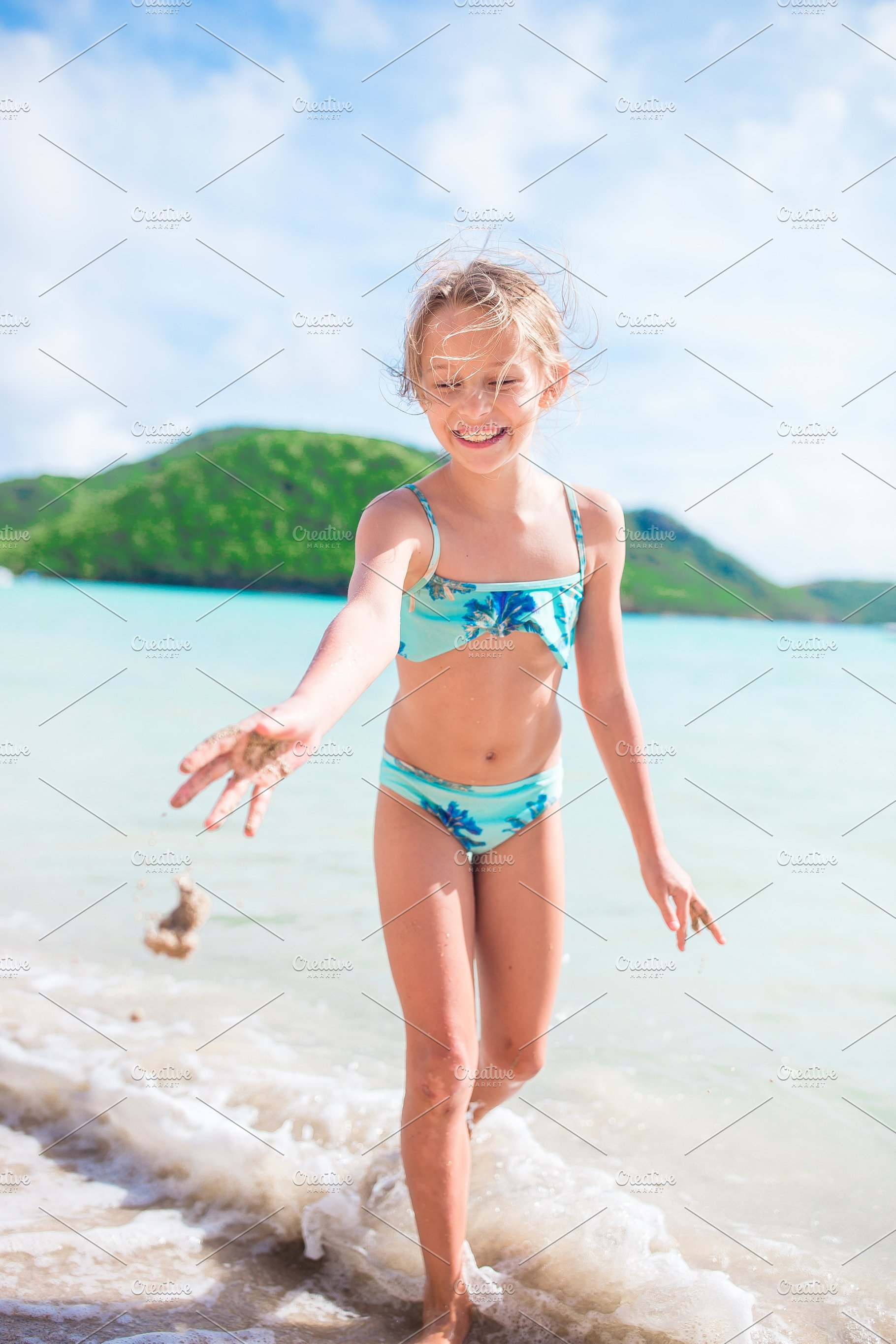 c41eed3a2c28 Little happy girl splashing and having fun in the shallow water. Kid ...