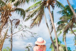 Young slim woman in bikini and straw hat on tropical beach. Beautiful girl under the palm tree on tropical Carlisle bay beach with white sand and turquoise ocean water at Antigua island in Caribbean