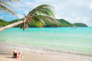 Young slim woman in bikini and straw hat lying on tropical beach. Beautiful girl under the palm tree in shallow water