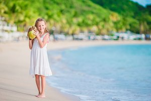 Little adorable girl with big coconut on the beach