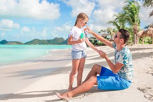 Young father applying sun cream to daughter nose on the beach. Sun protection