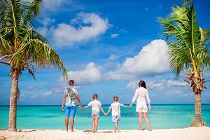 Back view of family of four in white on the beach on caribbean vacation. Parents with two kids enjoy their caribbean vacation on Antigua island