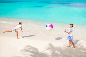 Little adorable girls playing with ball on the beach