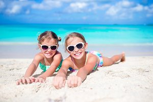 Close up little girls on sandy beach. Happy kids lying on warm white sand