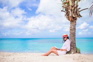 Young woman reading book during tropical white beach