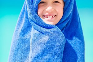 Portrait of smiling little girl wrapped in towel at tropical beach after swimming in the sea