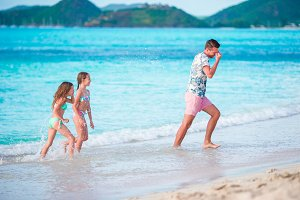 Happy father with kids play on beach. Happy family having fun during summer beach vacation