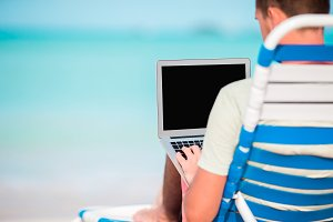 Young man with laptop on tropical caribbean beach. Close up computer in male hands