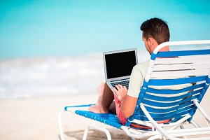 Young man with laptop on tropical caribbean beach. Man sitting on the sunbed with computer and working on the beach