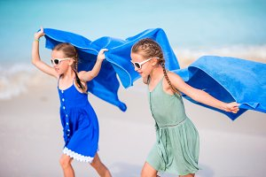 Cute little girls having fun running with towel and enjoying vacation on tropical beach with white sand and turquoise ocean water