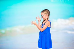 Cute little girl in dress at beach having fun. Funny girl enjoy summer vacation.