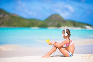 Little girl listening to music on headphones on the beach