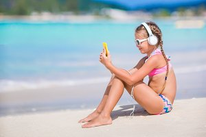 Little girl listening to music on headphones on the beach. Adorable kid enjoy music on the seashore