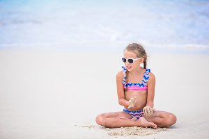 Adorable little girl playing with sand on the beach. Kid sitting in shallow water and making a sandcastle