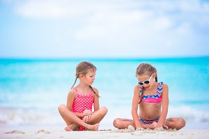 Adorable little girls playing with sand on the beach. Kids sitting in shallow water and making a sandcastle