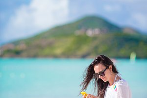 Young woman talking on phone during tropical beach vacation. Beautiful girl on the beach with cellphone on caribbean island