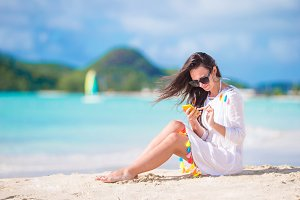 Young woman with phone on tropical beach. Beautiful girl on the beach with cellphone on caribbean island