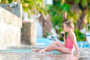 Little girl in outdoor swimming pool enjoy her vacation with tasty drink