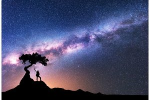 Milky Way and silhouette of woman under the tree
