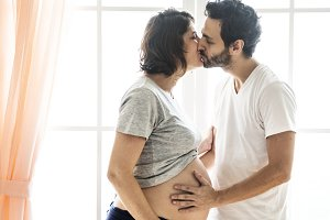 Pregnant woman and husband kissing
