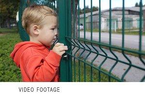 Little boy peering through a wire