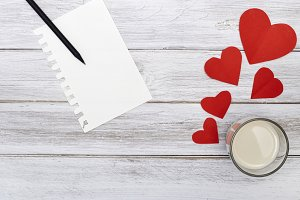 notepad pencil and two red hearts