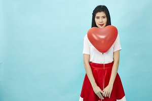 Woman holding big red balloon heart