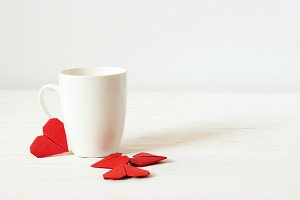 White cup and origami red hearts.