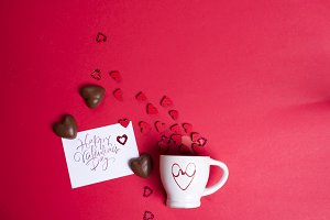Delicious chocolate candies and cup on red background