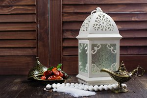 Arabic lantern, dates, aladdin lamp and rosary on wooden background